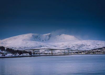 Snødekte fjell og blått hav