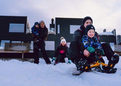 Barn og voksne ute og leker i snøen