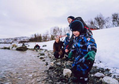 Barn og voksne ute i fjæra for å leke
