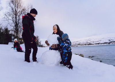 Barn og voksne som leker i snøen